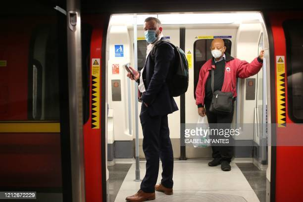 Passengers wearing PPE including face masks as a precautionary measure against COVID19 travel on a London Underground Tube train in the evening rush...