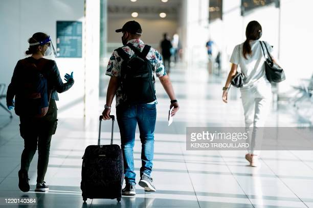 Passengers wearing protective face masks arrive at Brussels Airport, in Zaventem, on June 15, 2020 as Brussels Airport reopens for travels within...
