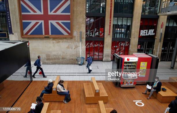 "Passengers wearing protective face masks await their train next to a painting of United Kingdom flag at the ""Gare du Nord"" train station as the..."
