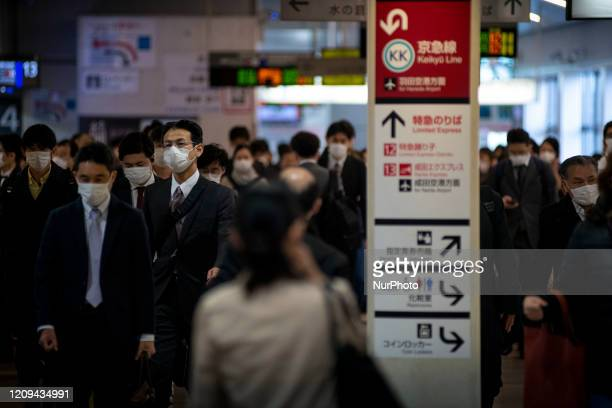 Passengers wearing protective face masks following an outbreak of the coronavirus disease are seen at a station after the government announced the...