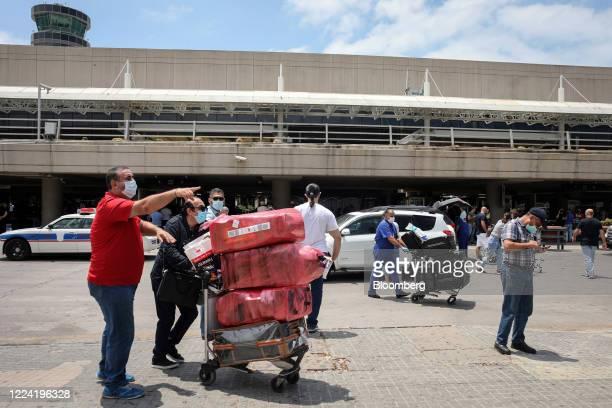 Passengers wearing protective face masks push luggage carts outside the terminal at Rafik Hariri International Airport in Beirut, Lebanon, on...