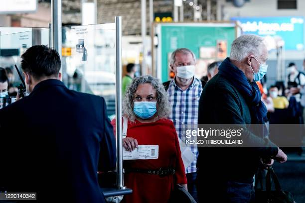 Passengers wearing protective face masks queue at the boarding gate at Brussels Airport, in Zaventem, on June 15, 2020 as Brussels Airport reopens...