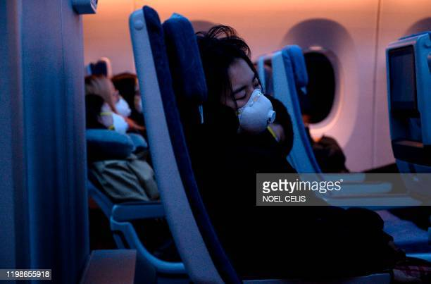 TOPSHOT Passengers wearing protective face masks sleep on their flight to Shanghai on February 4 2020 The new coronavirus that emerged in a Chinese...