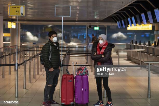 Passengers wearing protective face masks stand at Schiphol Airport in Amsterdam on March 13 amid an outbreak of COVID19 the new coronavirus The...