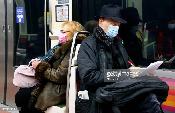 Passengers wearing protective face masks travel on a subway train before the 6 pm city-wide night time curfew during the coronavirus pandemic on...