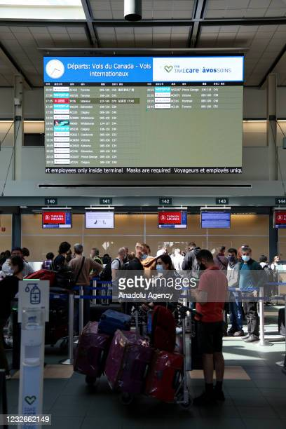 Passengers wearing protective face masks wait to check in and drop off their luggages at Turkish Airlines counters before their flights to Istanbul,...