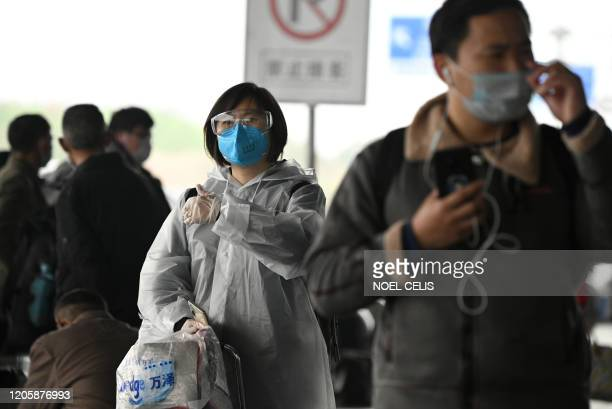 Passengers wearing protective facemaks arrive at the Changsha railway station in Changsha, the capital of Hunan province on March 8, 2020. / AFP...