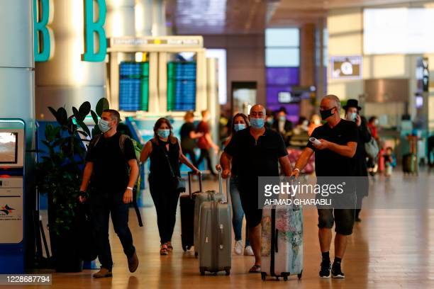 Passengers, wearing protective facemasks, are pictured at Israel's Ben Gurion Airport in Lod, east of Tel Aviv, on September 24 during the...