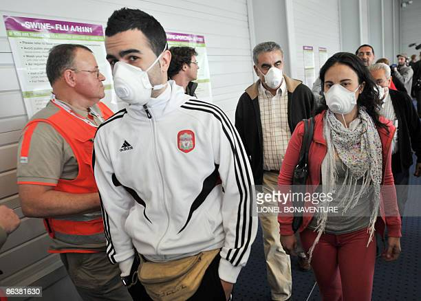 Passengers wearing protective masks arrive from Mexico at the RoissyCharles de Gaulle airport outside Paris on May 5 2009 Even as the swine flu's...