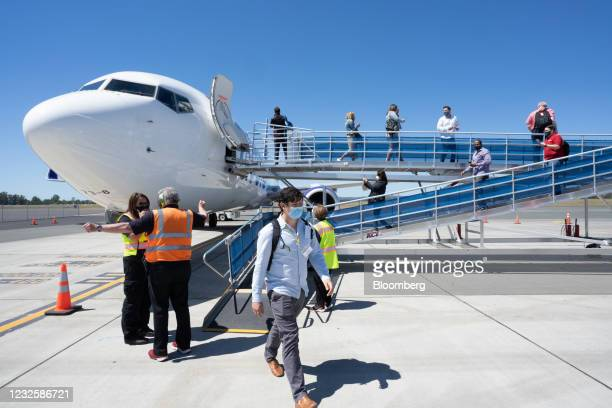 Passengers wearing protective masks disembark after the Avelo Airlines inaugural flight at Charles M. SchulzSonoma County Airport in Santa Rosa,...