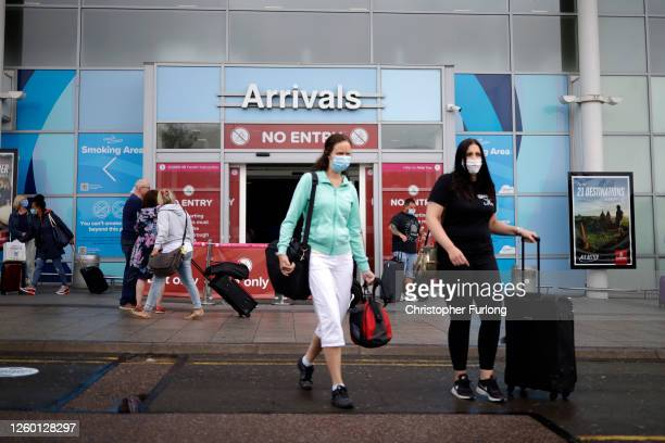 Passengers wearing protective masks exit the arrivals terminal at Birmingham Airport on July 27, 2020 in Birmingham, England. On Sunday the British...