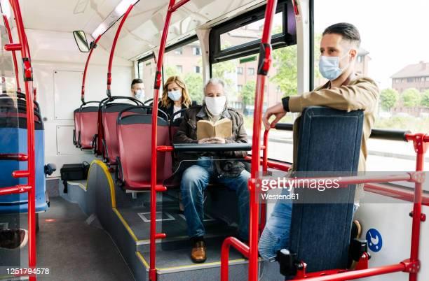 passengers wearing protective masks in public bus, spain - trasporto pubblico foto e immagini stock