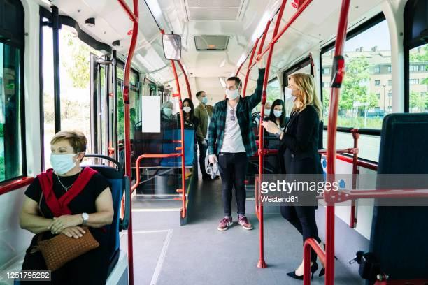 passengers wearing protective masks in public bus, spain - bus stockfoto's en -beelden