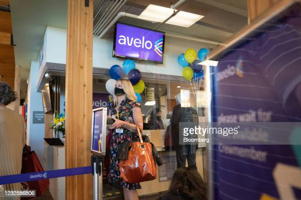 Passengers wearing protective masks queue to check in for an Avelo Airlines flight at Charles M. SchulzSonoma County Airport in Santa Rosa,...
