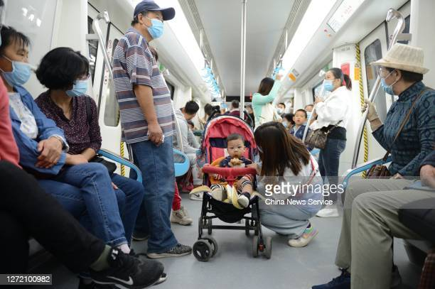 Passengers wearing protective masks ride a subway train during its test run on the Metro Line 2 on September 12, 2020 in Hohhot, Inner Mongolia...