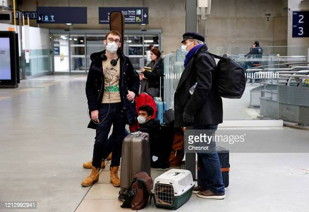 Passengers wearing protective masks wait for a train at the Montparnasse station as many Parisians come to the stations of the capital to try to take...