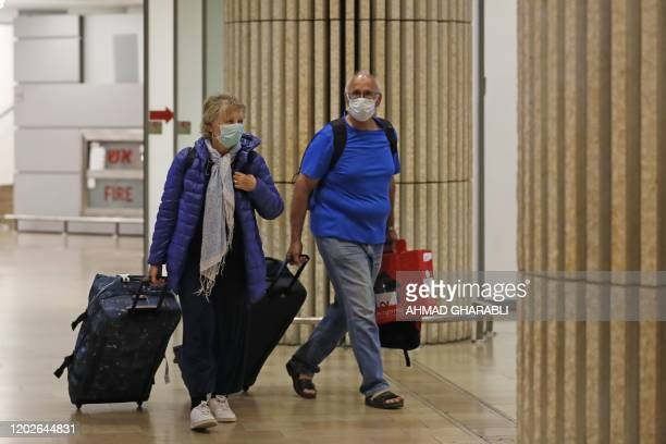 Passengers wearing protective masks walk at the arrival hall of Ben Gurion International Airport on February 22, 2020. - Israel refused to allow some...