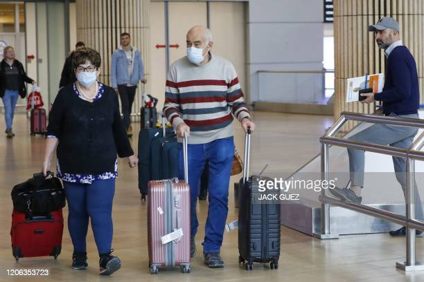 Passengers wearing protective masks walk at the arrival hall of Ben Gurion International Airport near Tel Aviv, on March 10, 2020 amid major...