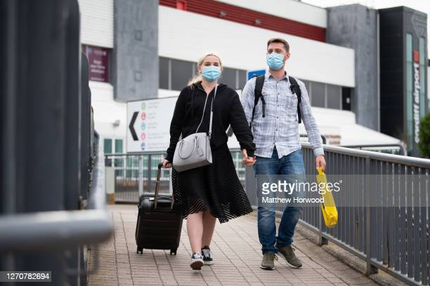 Passengers wearing surgical masks leave Cardiff Airport after departing a Ryanair flight from Faro, Portugal on September 4, 2020 in Cardiff, Wales....
