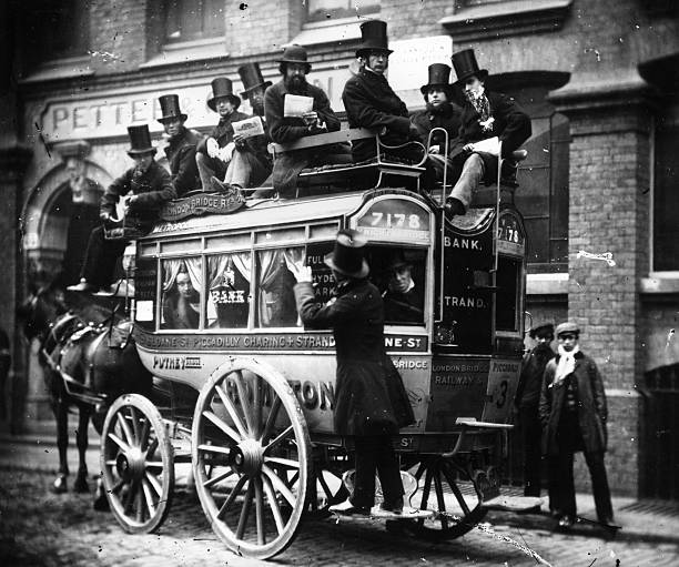 Passengers wearing top hats on a 'knifeboard' omnibus...