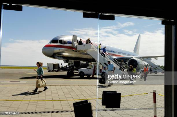 Passengers with carry-on bags disembarking from a American Airlines Boeing 757-200 parked on the ground..