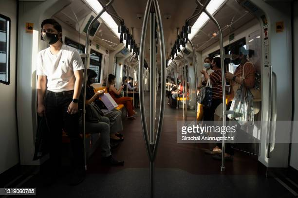 Passengers with face masks ride the BTS skytrain through the central business district on May 20, 2021 in Bangkok, Thailand. As the third wave of the...