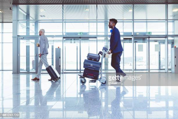 passengers with luggage at airport terminal - izusek stock pictures, royalty-free photos & images