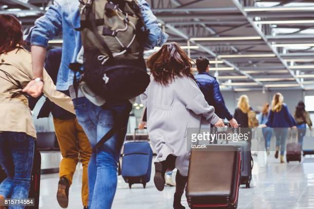 passengers with luggage in airport corridor - urgency stock pictures, royalty-free photos & images