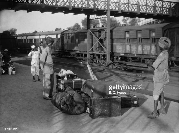 Passengers with luggage waitiing for the train at Agra Railway Station, Uttar Pradesh, 1929.