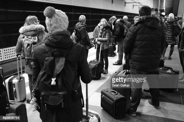 Passengers with their suitcases wait for a delayed highspeed train of German state railways Deutsche Bahn to Munich following the cancellation of...