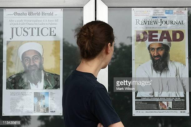 Passer by looks at newspaper headlines reporting the death of Osama Bin Laden, in front of the Newseum, on May 2, 2011 in Washington, DC. Last night...