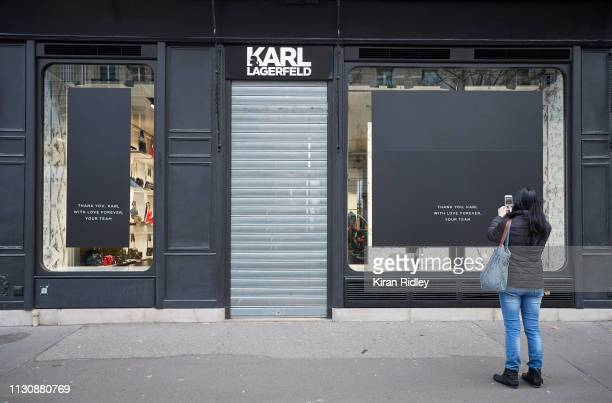 A passer by takes photographs of Karl Lagerfeld's first own brand boutique in St Germain des Prés Paris which windows pay tribute to the legendary...