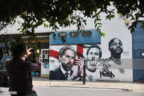 Passer by takes photos of the mural of England football manager Gareth Southgate and players Harry Kane and Raheem Sterling, with the words 'You Did...