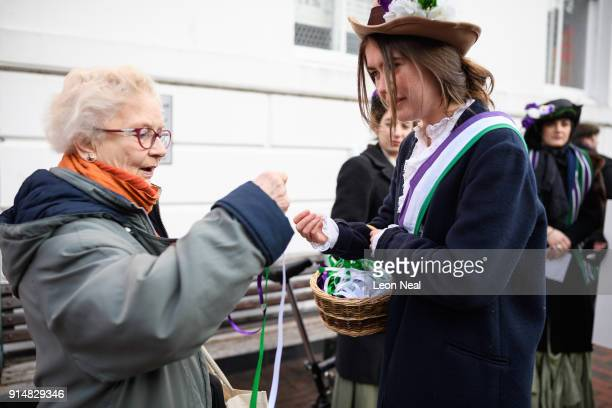 A passerby accepts a coloured ribbon from student Hope Williams while a group recreate a suffragette protest march through the town centre at Royal...