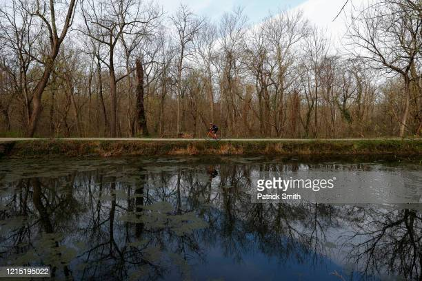 A passerby exercises alone as they ride a bicycle near the Potomac River on March 26 2020 in Brookmont Maryland While Maryland Gov Larry Hogan...
