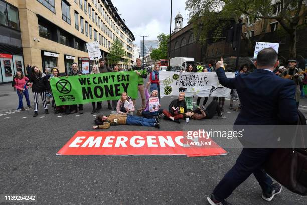 A passerby gives a thumbs up to Environmental campaigners from the Extinction Rebellion group block a junction at London Wall by Deutsche bank as...