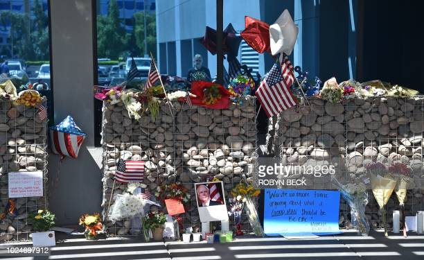 A passerby is reflected in glass as he collects himself before a makeshift memorial to Senator John McCain outside McCain's office in Phoenix Arizona...