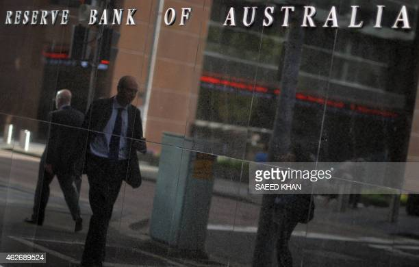 A passerby is reflected on a wall of the Reserve Bank of Australia in Sydney on February 3 2015 Australia's central bank on February 3 lowered its...