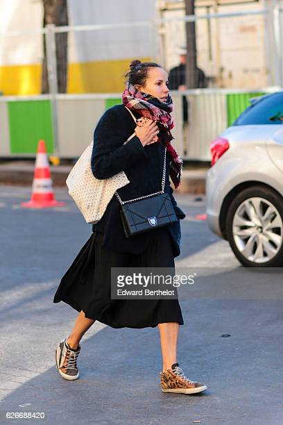 A passerby is wearing a balck Dior bag a large scarf a black coat outside the Grand Palais during the Victoria Secret show on November 30 2016 in...