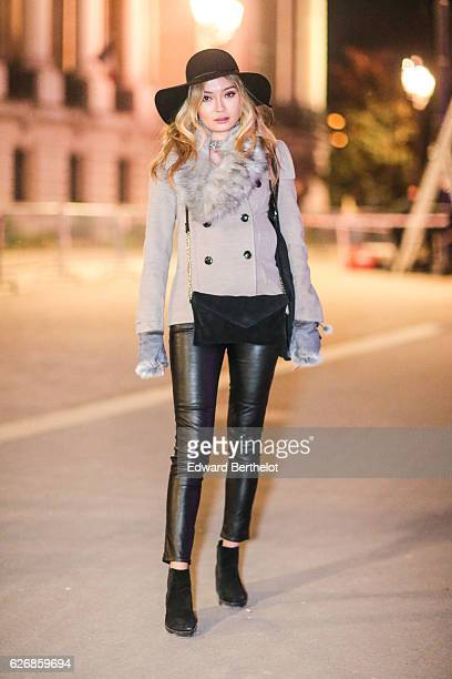A passerby is wearing a black hat a gray scarf a white coat black leather pants and black shoes outside the Victoria's Secret Fashion show at the...