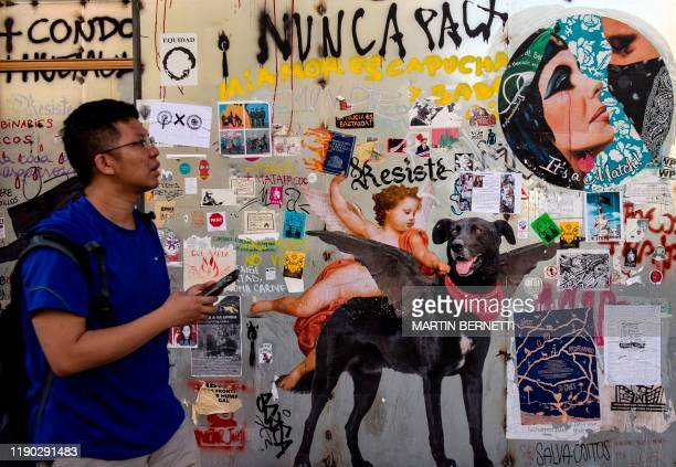 A passerby looks at a mural with the image of the socalled Negro Matapacos dog in Santiago on December 13 2019 The social movement that broke out in...