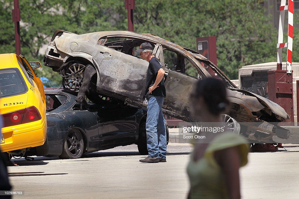 A passerby looks on as workers stage a car accident on the