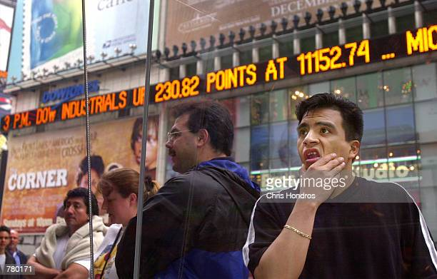 A passerby looks over the prices on the Nasdaq board in Times Square in New York April 3 2000 The Nasdaq plummeted 349 points to 422525 Monday the...
