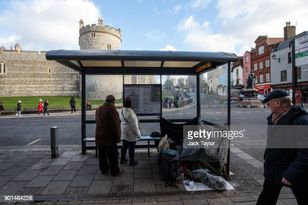 A passerby looks towards a homeless person's belongings in a bus shelter outside Windsor Castle on January 5 2018 in Windsor England British Prime...
