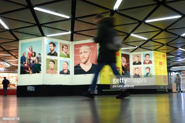 A passerby passes portraits of ensemble members of the theatre in the underground station WillyBrandtPlatz in Frankfurt am Main Germany 05 October...
