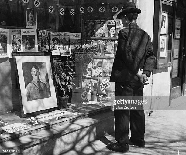 A passerby pauses to view a variety of Nazi propaganda material displayed in a shop window in the Austrian town of Innsbruck 1938
