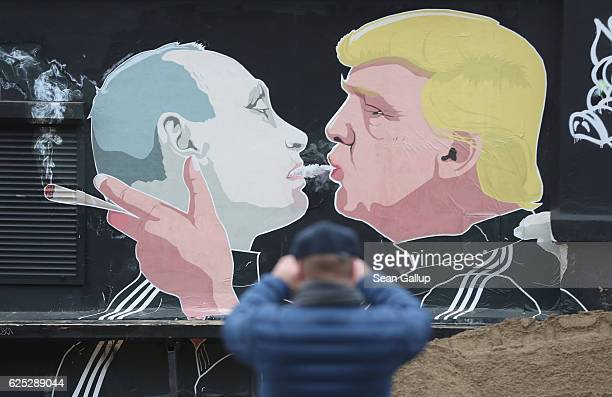 A passerby photographs a mural showing US Presidentelect Donald Trump blowing marijuana smoke into the mouth of Russian President Vladimir Putin on...