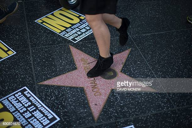 A passerby stomps on the Hollywood Walk of Fame star for Donald Trump as people protest in reaction against a Twitter post by US Presidentelect Trump...
