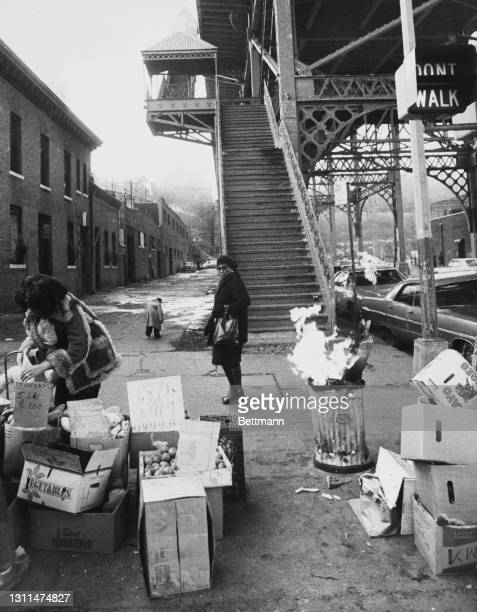 Passer-by stops to inspect the produce on offer by a fruit seller at a makeshift stand, a fire burning in a trash can, near an overpass at 155th...