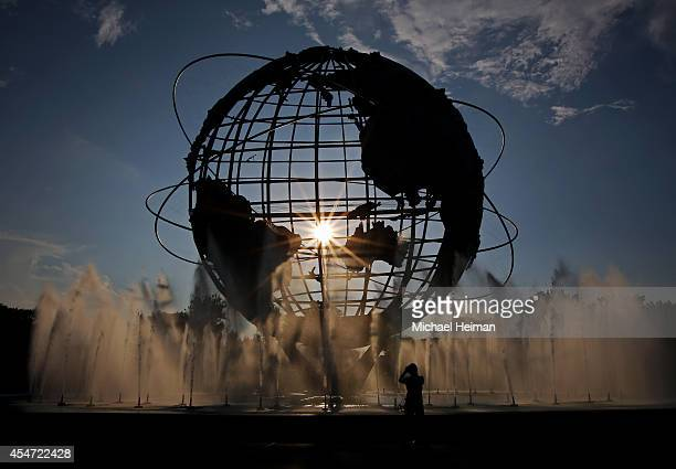 Passerby takes a photo as the sunsets behind the unisphere on Day Twelve of the 2014 US Open outide of the USTA Billie Jean King National Tennis...